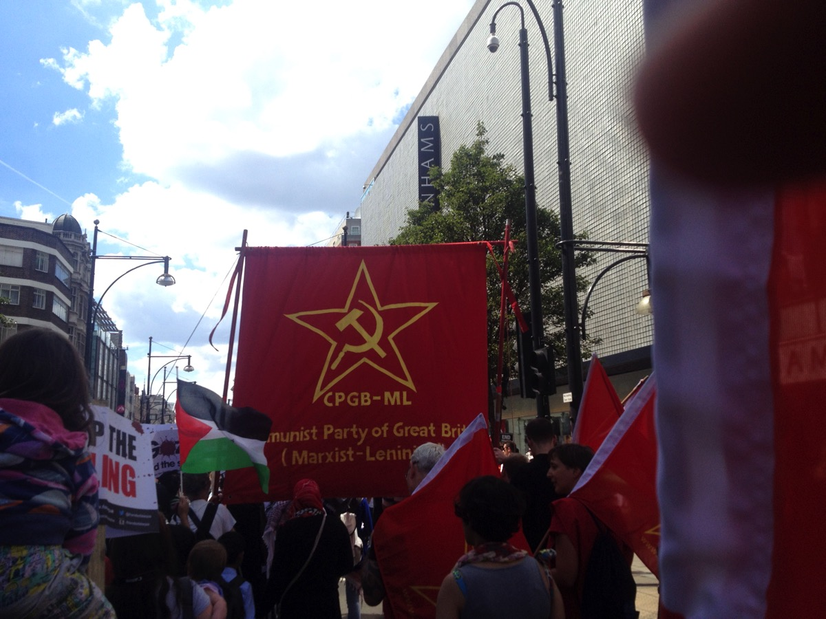 March with banner showing 'CPGB-ML Communist Pary of Great Britain (Marxist-Leninist)'