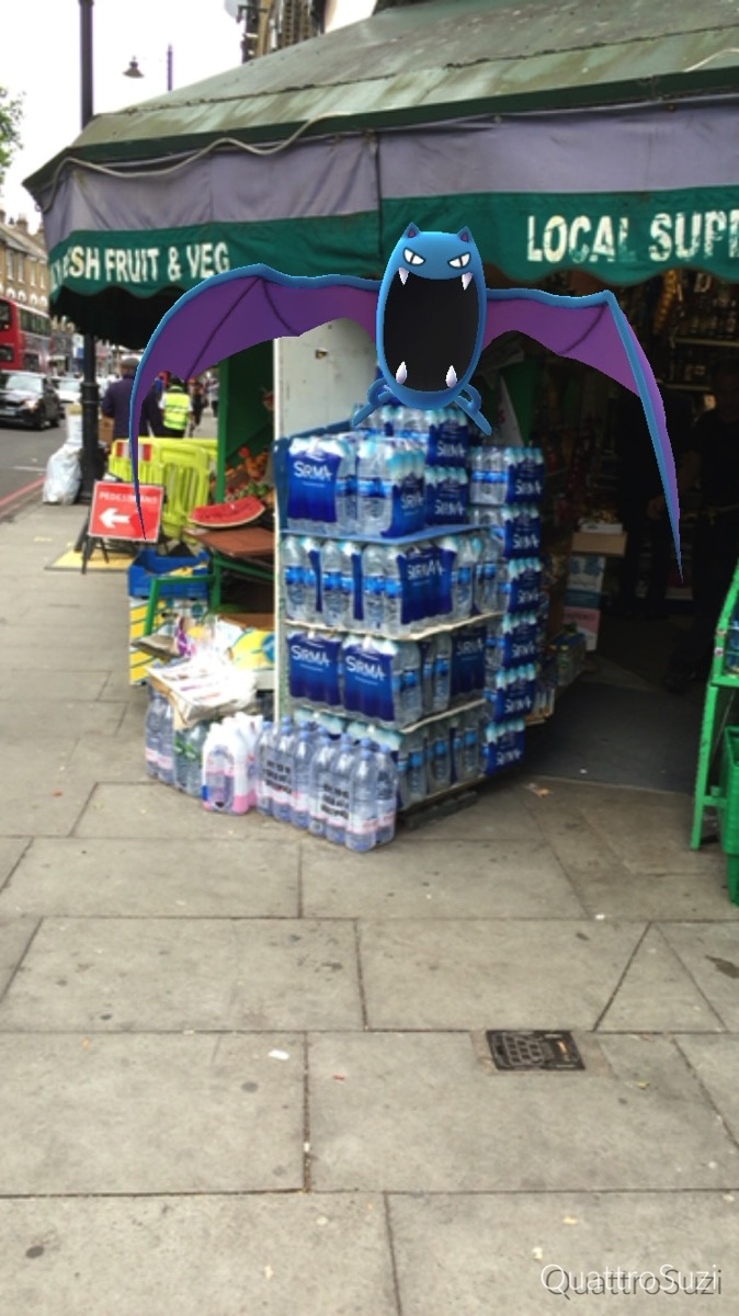 A hovering Golbat superimposed on a shop called 'Local Supermarket'.