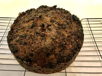A Christmas cake (rich fruit cake) sitting on a cooling rack.